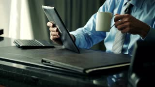businessman-reading-something-on-tablet-computer-by-desk-at-office_vy33h47lg__S0000